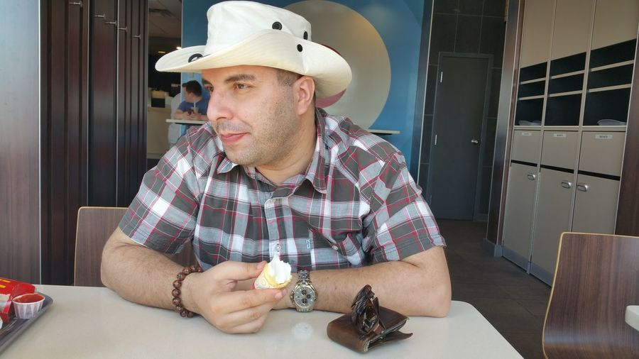 Mid Adult Man Wearing Hat Eating Food While Sitting In Cafe