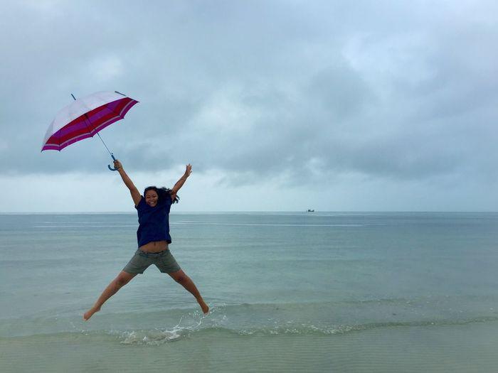 Woman jumping on beach against sky