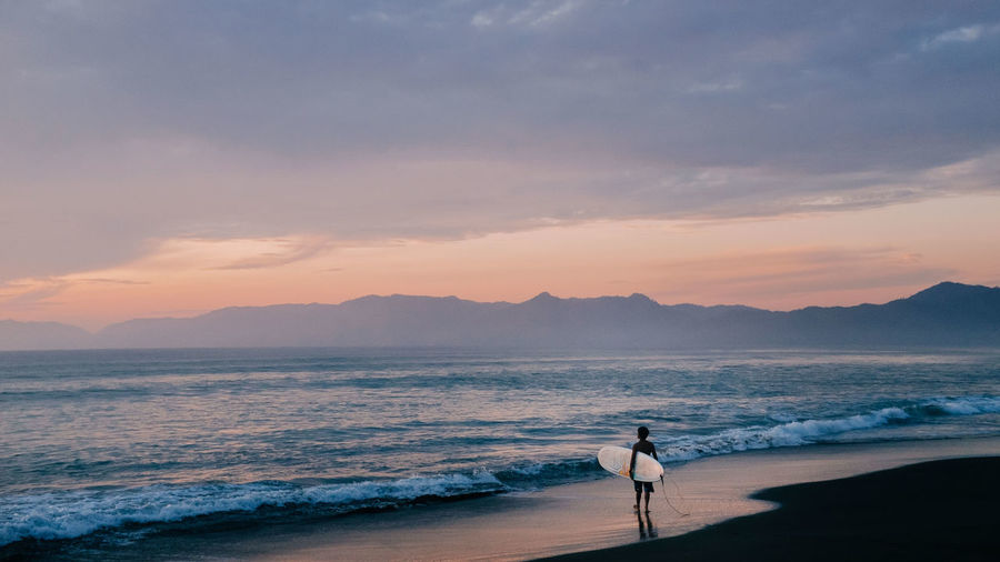 A surfer stands on the beach, looking out at the waves at sunset. Beach Beauty In Nature Dusk Freedom Inspiration Motivation Nature Ocean One Man Only One Person Outdoors Pastel Shore Standing Sunset Surf Surfboard Surfer Surfing Waves