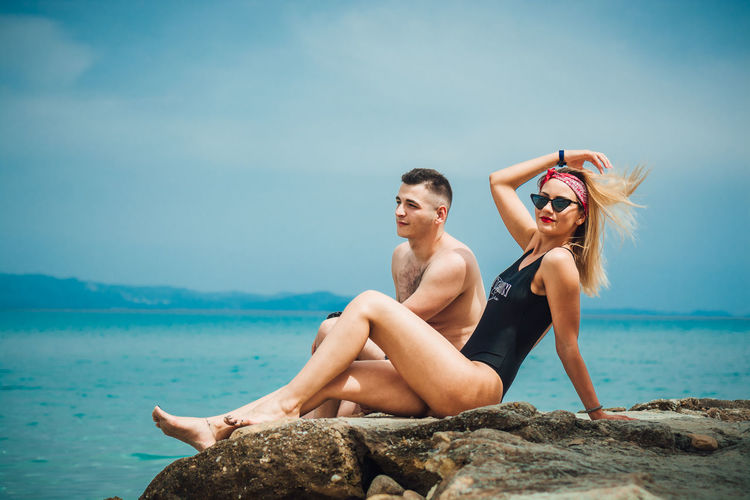 Young couple on sea shore against sky