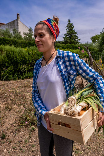 Smiling woman holding vegetables standing at farm