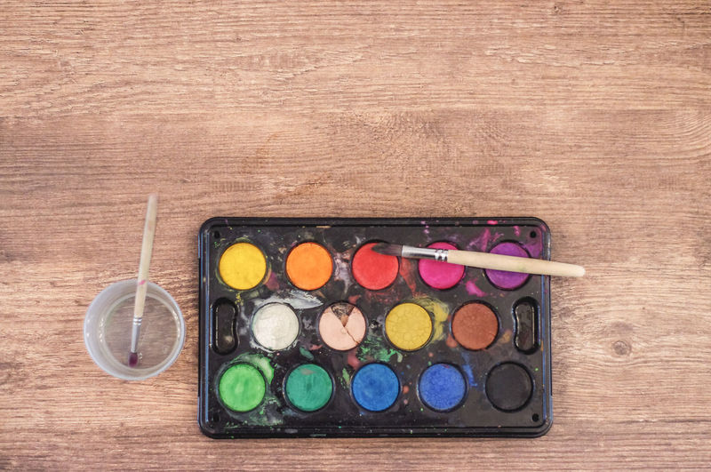 Watercolours and paint brushes on wooden tabletop Artistic Colourful Copy Space Green Orange Paint Brush Pink Red Art Black Blue Brown Directly Above Handicrafts Multi Colored No People Painting Palette Tabletop Watercolor Watercolours White Wood - Material Yellow