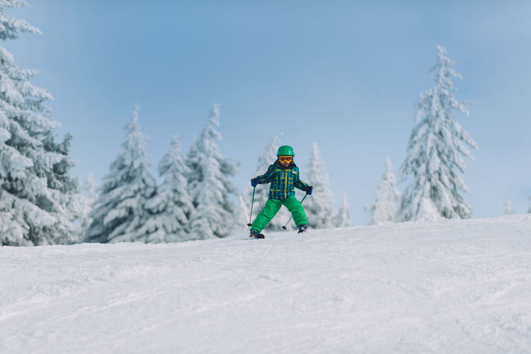 Full length of boy skiing on snow covered land