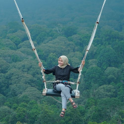 Full length of woman sitting on swing against forest