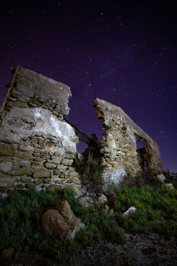 Low angle view of abandoned building against star field sky at night