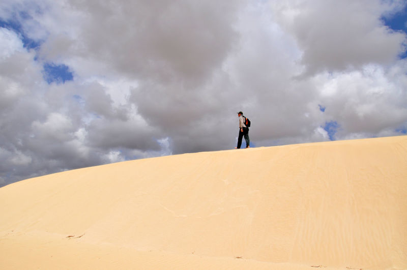 Low Angle View Of Man Walking At Desert Against Cloudy Sky