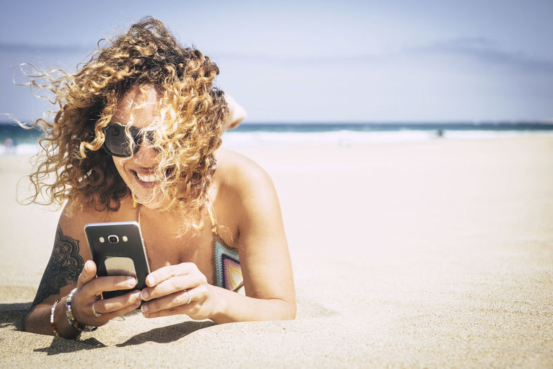 Cheerful Woman Using Phone While Lying At Beach