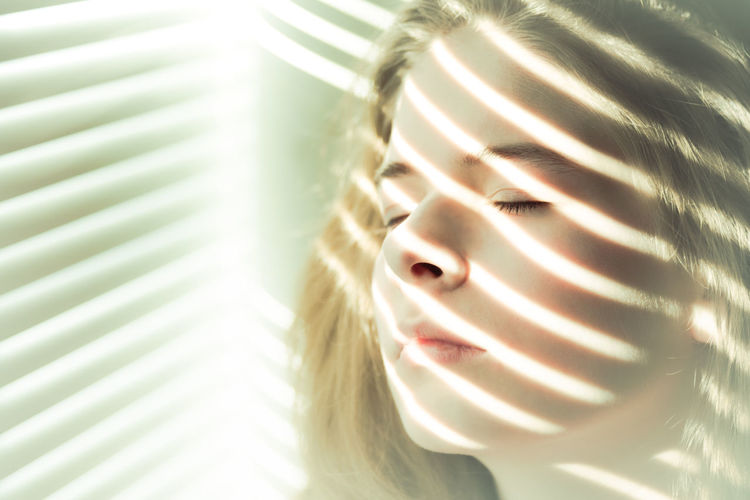 Close-up portrait of girl with eyes closed standing by window with light and shadow stripes of sun shining through blinds onto her face Beautiful Bright Calm Eyes Closed  Light Natural Light Peace Soft Stripes Sunlight Tranquility Woman Blond Hair Close-up Diagonal Lines Female Girl Glowing Indoor Light And Shadow Portrait Restful Warm Yellow Zen