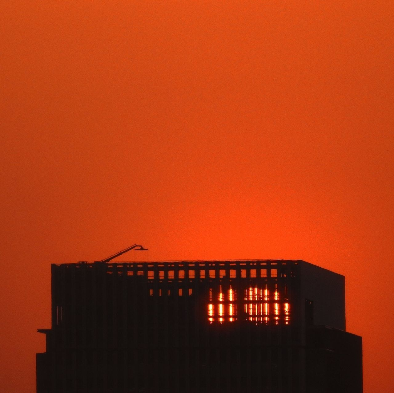 architecture, built structure, building exterior, orange color, sky, copy space, building, sunset, no people, clear sky, nature, silhouette, outdoors, illuminated, residential district, low angle view, industry, construction industry, city, house