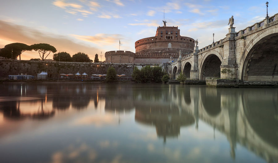 Castel santangelo over tiber river during sunset in city