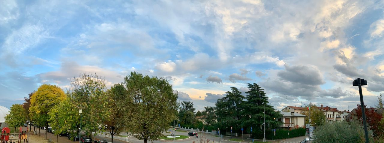 Panoramic shot of trees and buildings against sky