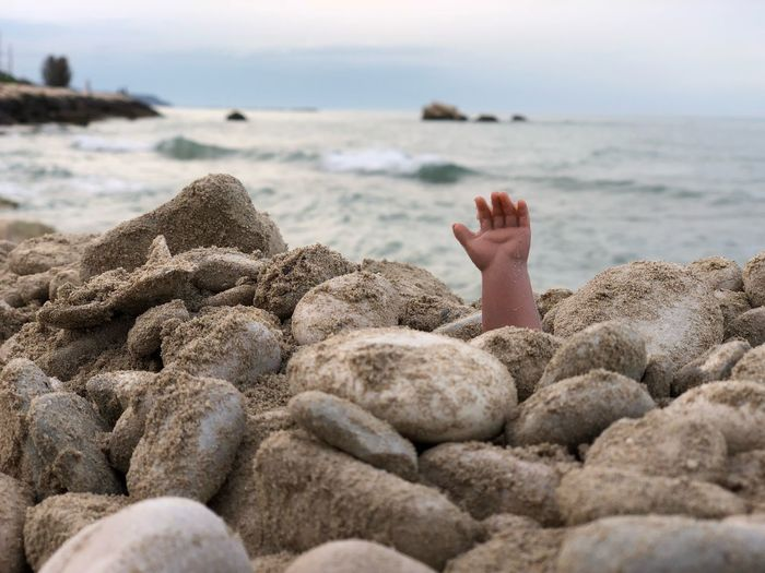 Person hand amidst pebbles at beach against sky