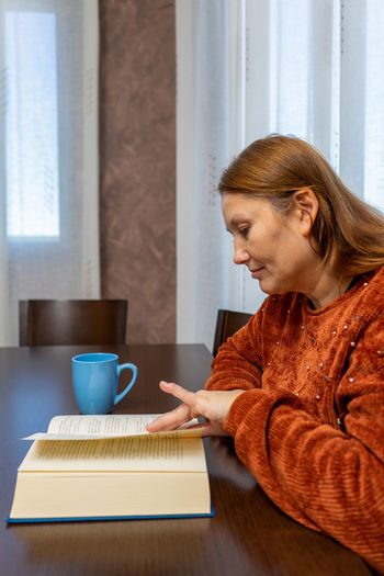 Mature woman drinking coffee while reading book at home