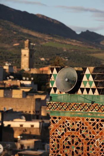 Megaphone on mosque against buildings at dusk
