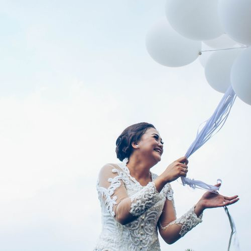 Cheerful bride holding helium balloons against sky
