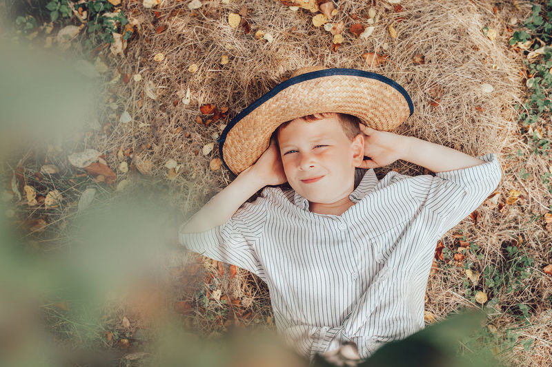 Little preschooler farmer in straw hat and rustic  shirt lies on the straw and yellow autumn leaves