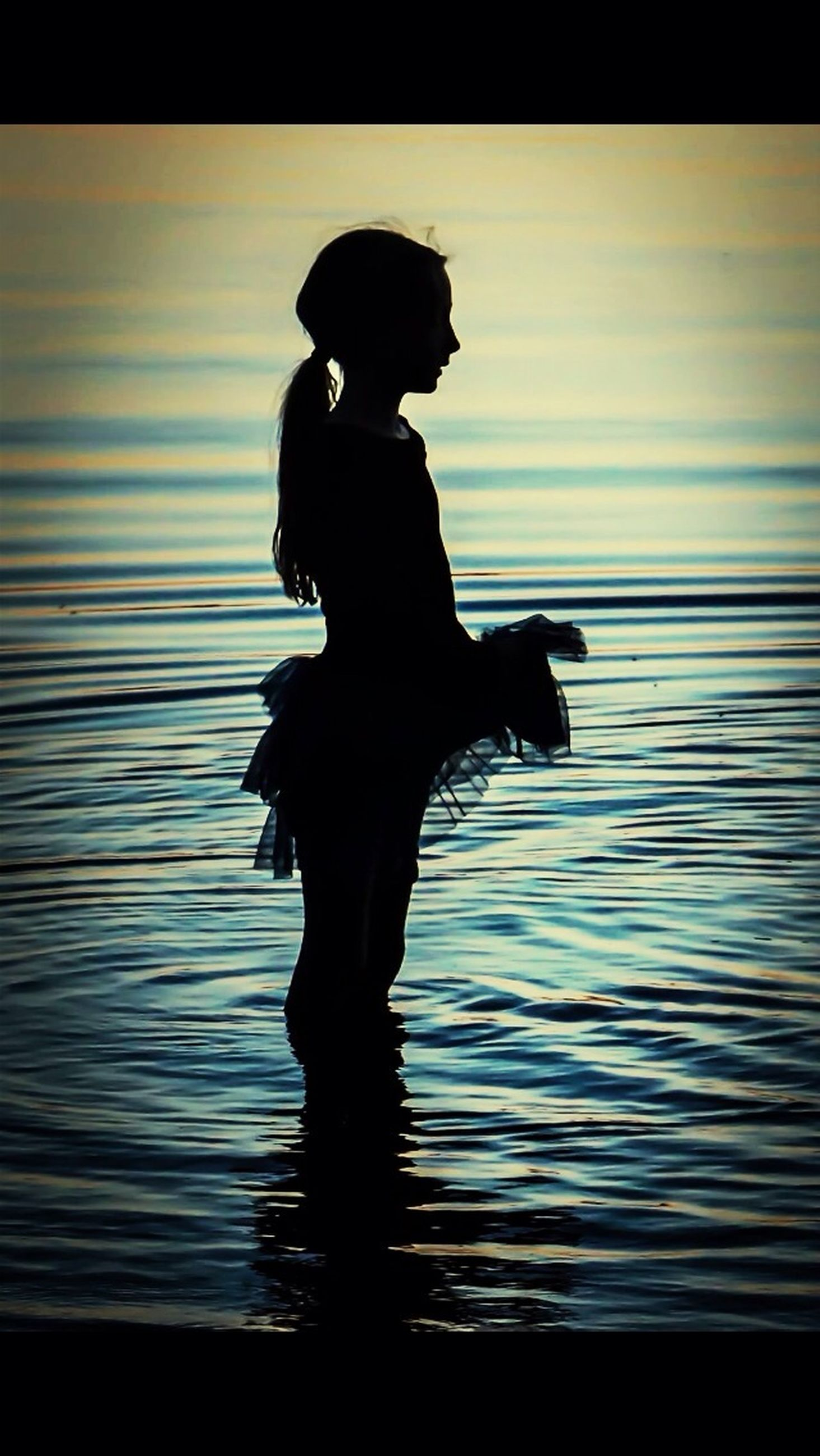 silhouette, water, sunset, standing, sea, full length, lifestyles, tranquility, leisure activity, reflection, sky, tranquil scene, beauty in nature, nature, outline, scenics, horizon over water, idyllic