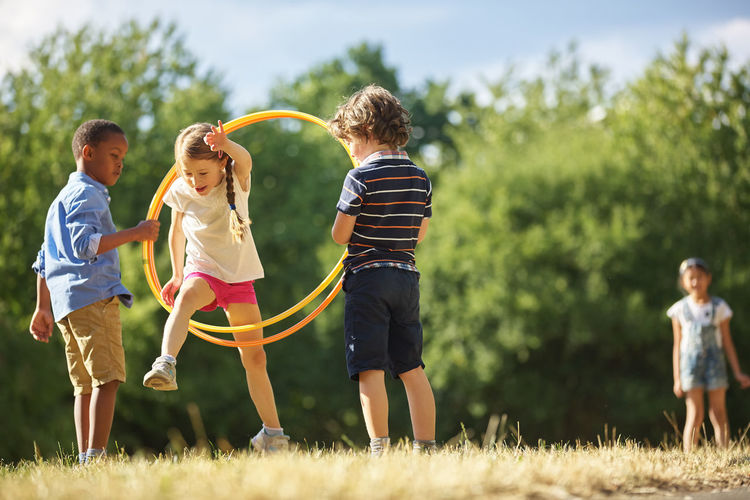 Friends Playing With Plastic Hoop On Field