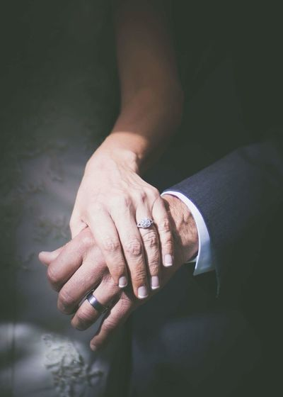 Midsection of bride holding groom hand