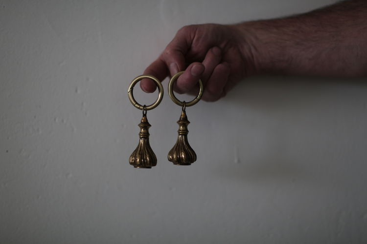 Cropped hand of man holding key rings by white wall
