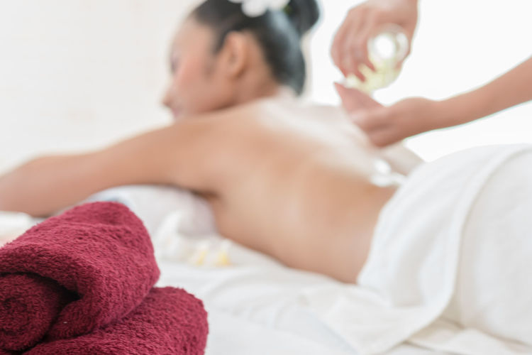 Cropped image of therapist pouring massage oil by woman lying at health spa