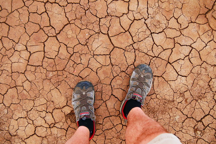 Cracked soil with legs and shoes Brown Close-up Crack Cracked Desert Dry Earth Extreme Feet Flowers Ground Growth High Angle View Landscape Landscapes With WhiteWall Legs Lifestyles Nature Pattern Sand Shoes Soil Summer Terrain Yellow Go Higher