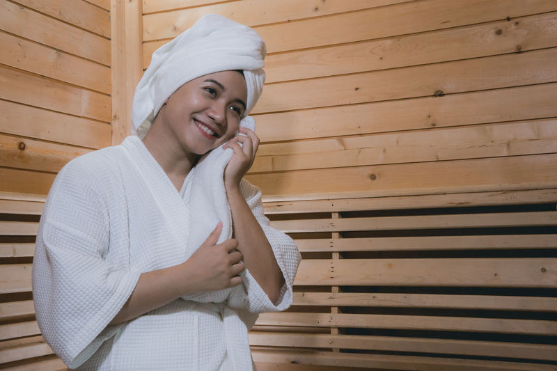 Smiling Woman Hair Wrapped In Towel While Sitting At Spa