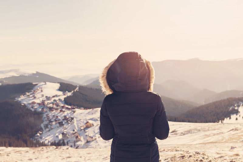 Rear view of woman standing on snow covered landscape against sky