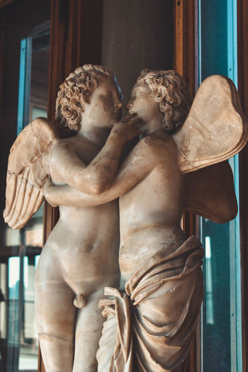 Angel Architecture Art And Craft Craft Creativity Day Female Likeness Focus On Foreground Human Representation Indoors  Male Likeness No People Representation Sculpture Shirtless Statue Window