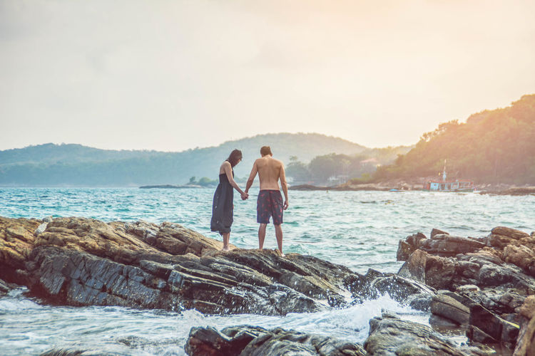 Couple Standing On Rock Formation At Beach Against Sky During Sunset
