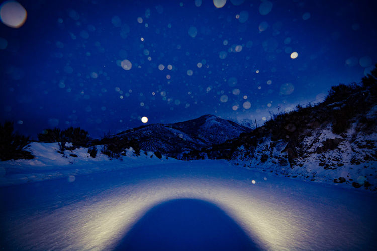 Scenic view of snowy landscape against sky at night
