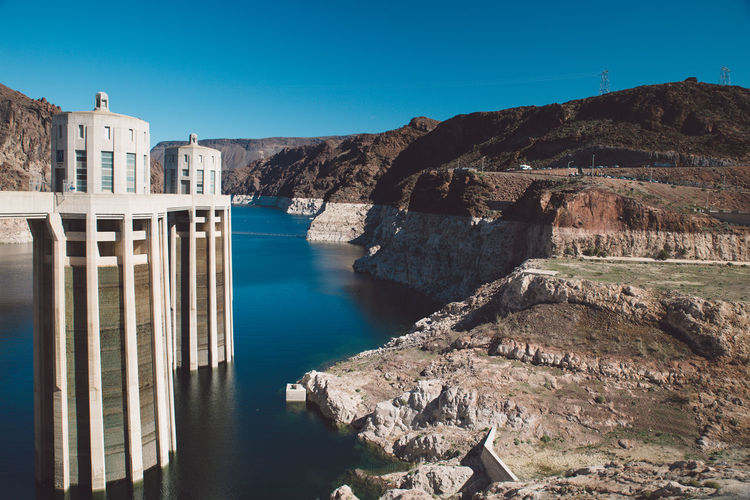 Hoover dam by rock formation against sky in arizona