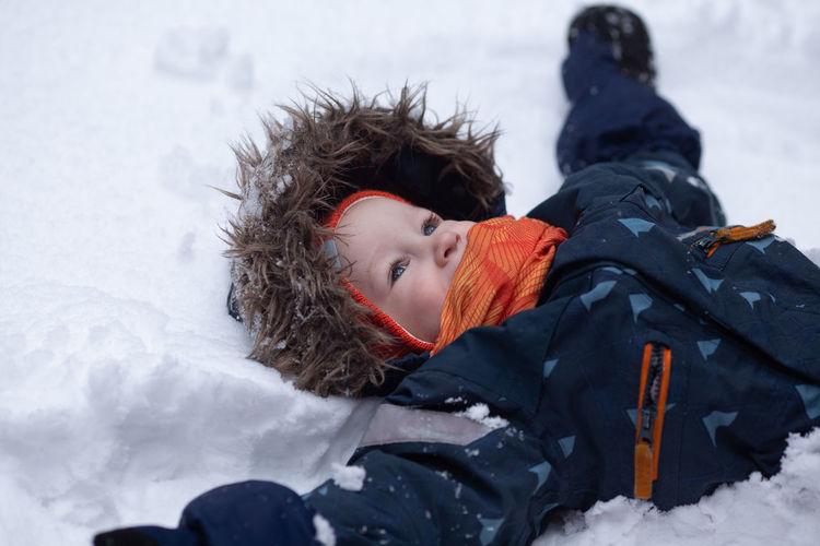 Portrait of boy lying in snow