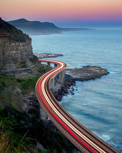 High angle view of light trails on bridge over sea during sunset