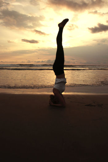 Full Length Of Woman Performing Headstand On Beach During Sunrise