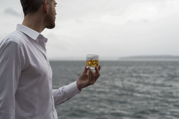 Whiskey in hand by the sea overcast landscape horizontal wealthy male longing look out to sea Alcohol Bourbon Clean Cruise Dram Gaze Glass Golden Hand Human Element Ice Lifestyle Longing Luxury Portrait Rocks Sailing Scotch Sea Shirt Tequila Wealth Whiskey White Yacht