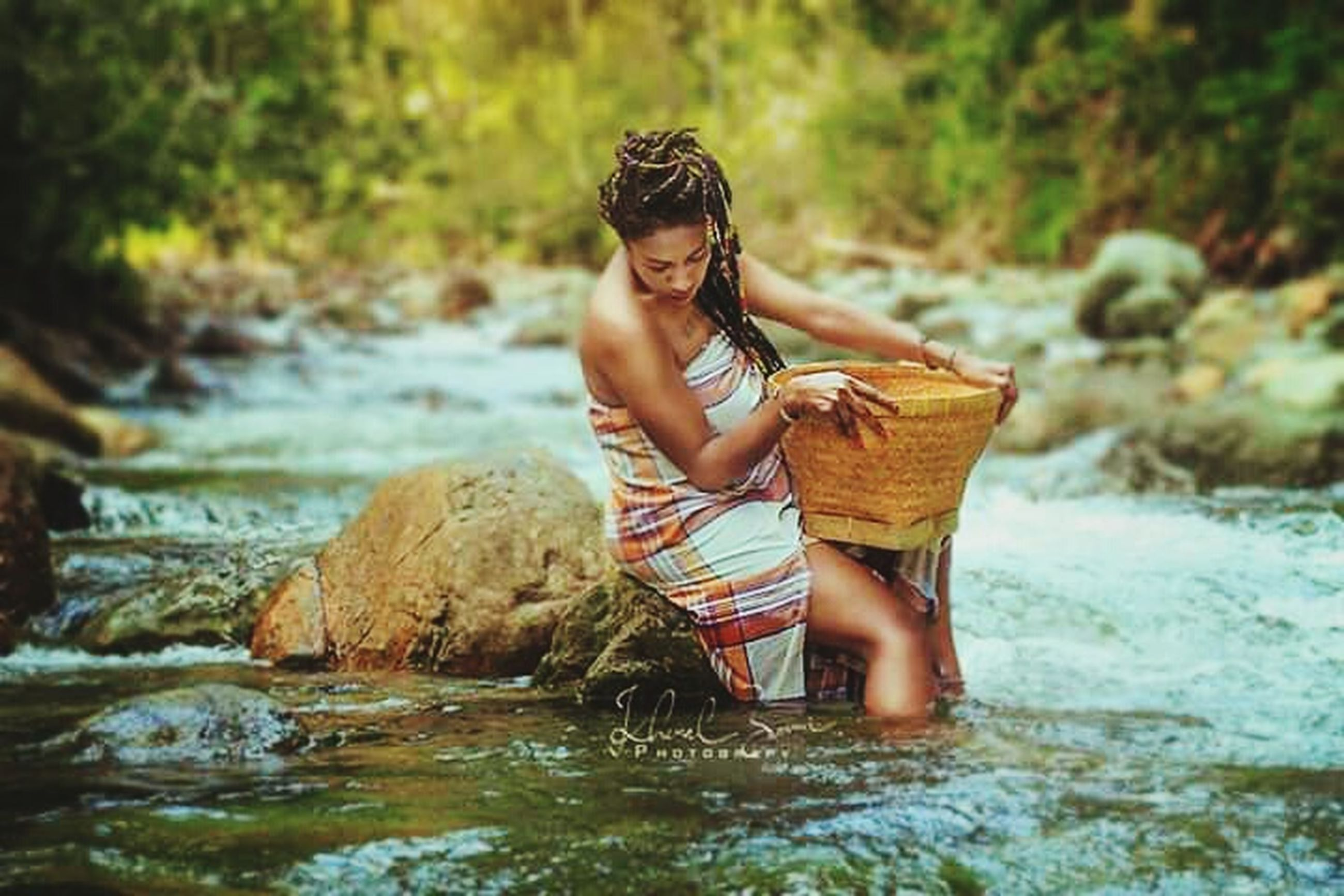 water, one person, real people, nature, full length, casual clothing, container, river, basket, front view, women, day, young adult, young women, lifestyles, sitting, outdoors, stream - flowing water, hairstyle