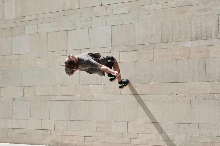 Side view of man jumping against wall