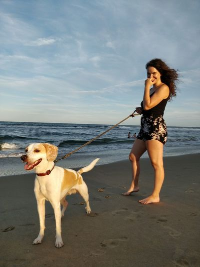 Animal Themes Beach Beautiful Woman Beauty In Nature Day Dog Domestic Animals Full Length Leisure Activity Lifestyles Mammal Nature One Animal One Person Outdoors Pets Real People Sand Sea Sky Smiling EyeEmNewHereWater Young Adult Young Women