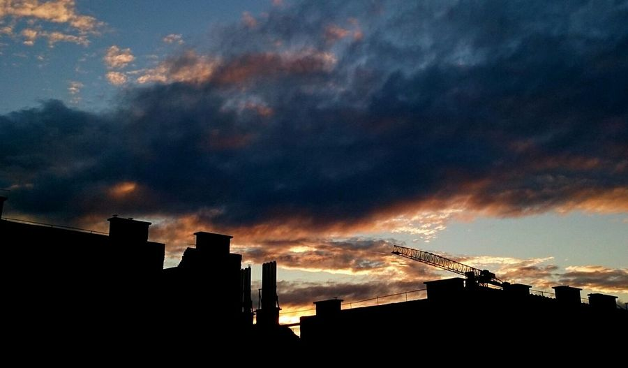 Buildings against cloudy sky at sunset