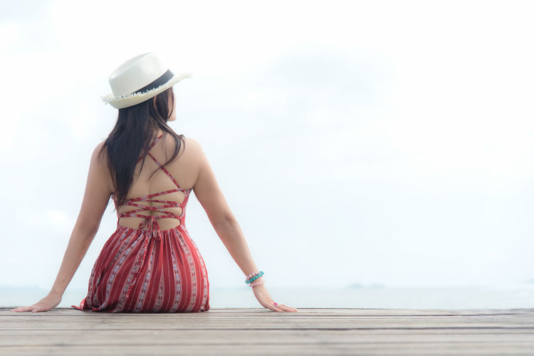 Rear view of woman wearing hat standing against sky
