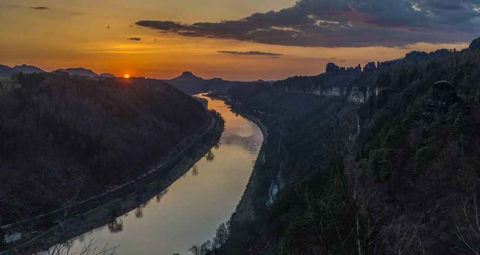 Panoramic view of river and mountains against sky during sunset