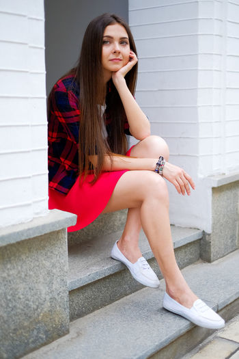 woman sitting on street wearing skirt and casual. One Person Real People Lifestyles Young Adult Young Women Beautiful Woman Hairstyle Portrait Potrait Of Woman Females Sexygirl Attractive Beautiful Long Hair Casual Clothing Casual Leisure Activity Lesiure Activity Relaxing Skirt Trendy Fashion Model Posing Romantic Dreaming Outdoors Steps And Staircases Sitting Hair Staircase Women Brown Hair
