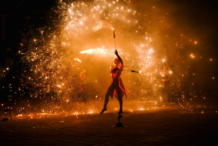 Full length of woman with fire crackers at night
