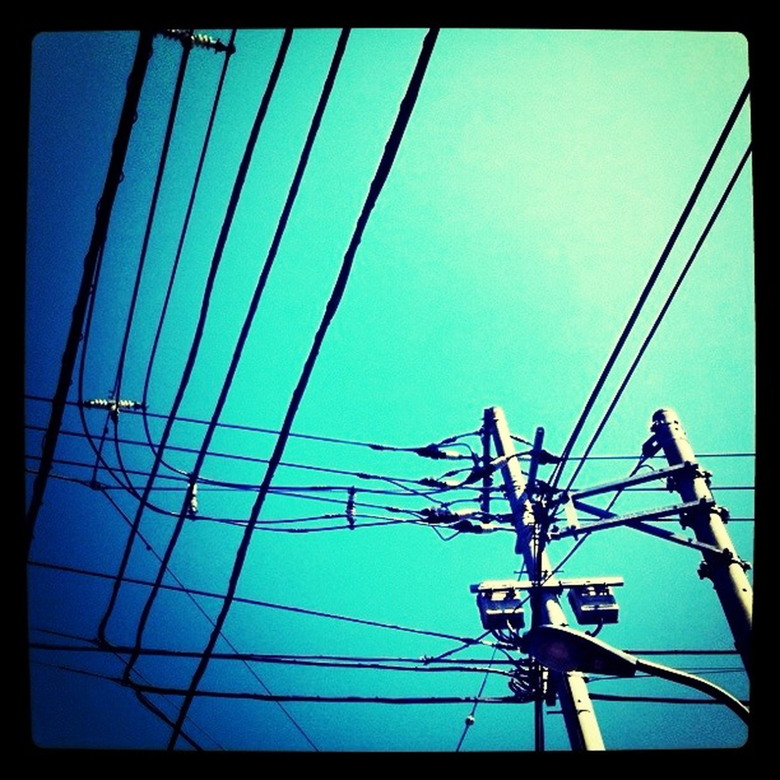 low angle view, power line, electricity pylon, power supply, electricity, connection, clear sky, fuel and power generation, blue, technology, cable, transfer print, sky, auto post production filter, power cable, day, silhouette, outdoors, no people, built structure