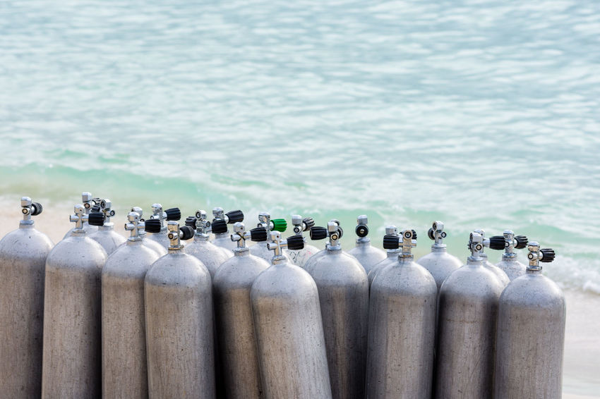 A collection of scuba divers air tanks on a tropical white sand beach. Scuba Diving Tropical Paradise Bottle Close-up Collection Day Diving Lesson Diving Tanks In A Row No People Outdoors Scuba Diver Scuba Diving Scuba Tanks Sea Tropical Climate Water