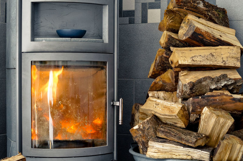 Logs by burning fireplace at home