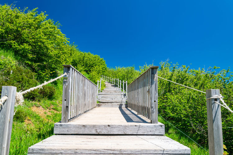 Empty footbridge against clear blue sky