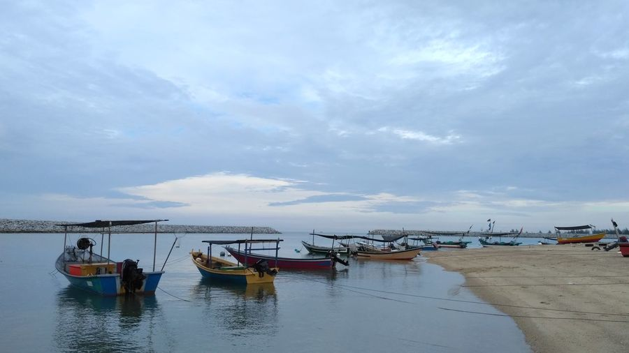 Fishing boats moored at shore against sky