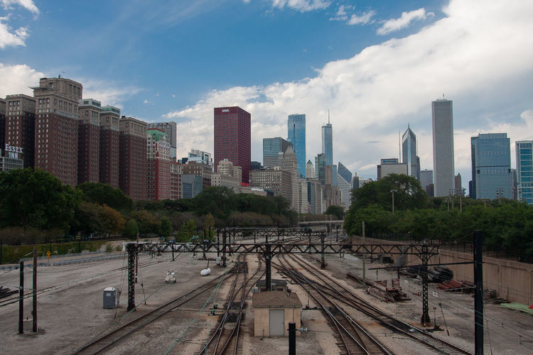Railroad tracks amidst buildings in city against sky